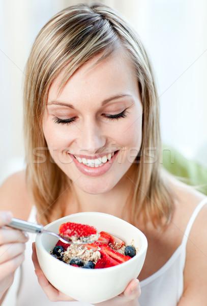 Lumineuses femme manger muesli fruits séance Photo stock © wavebreak_media
