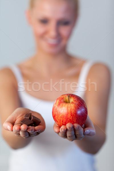 Beautiful woman holding chocolate and apple focus on apple  Stock photo © wavebreak_media