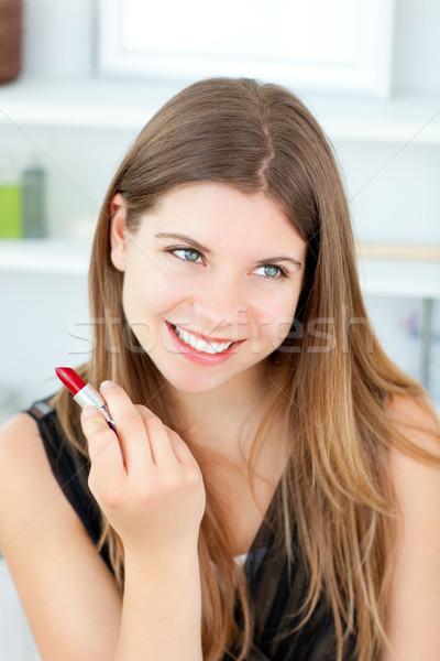 Beautiful girl using lipstick at home Stock photo © wavebreak_media
