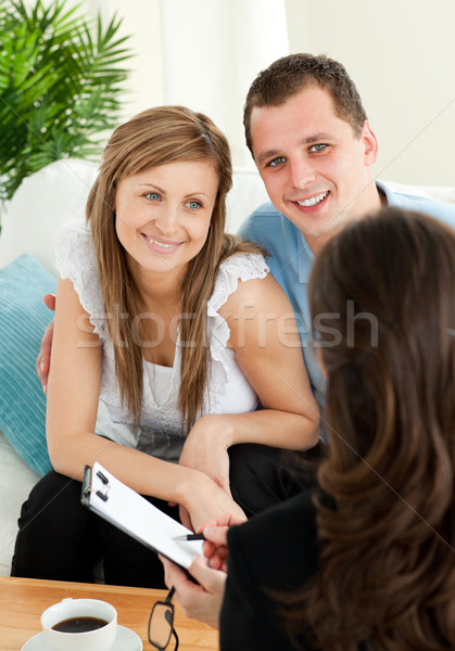 Bright couple concluding a car contract with a female dealer in the living room Stock photo © wavebreak_media