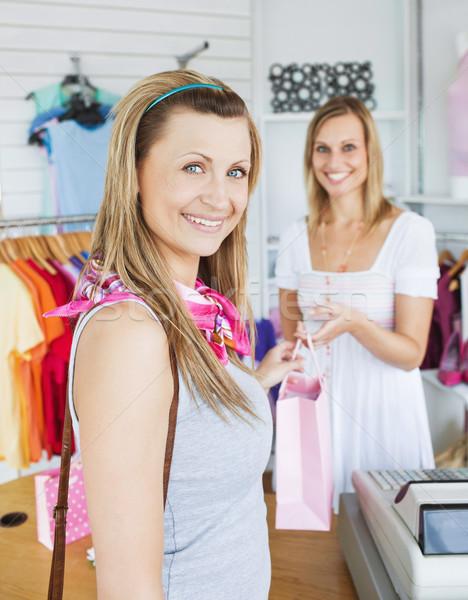 Mujer toma bolsa de la compra vendedora tienda Foto stock © wavebreak_media