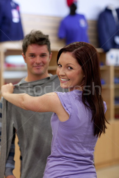 Happy couple looking for a sweat-shirt in a clothes store Stock photo © wavebreak_media