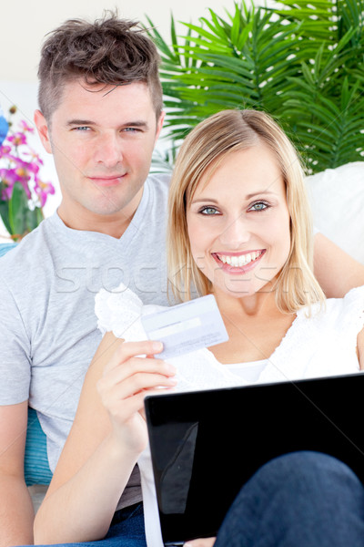 Enamored couple lying on the sofa with a laptop and a card at home Stock photo © wavebreak_media