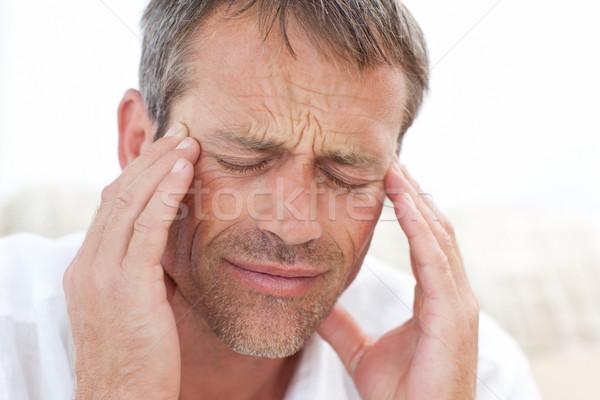 Man having a headache at home Stock photo © wavebreak_media