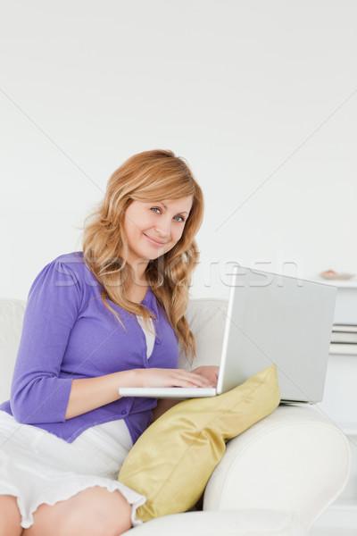 Atractivo mujer sesión sofá usando la computadora portátil casa Foto stock © wavebreak_media