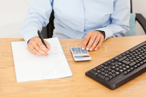 Female accountant writing results on a piece of paper in an office Stock photo © wavebreak_media
