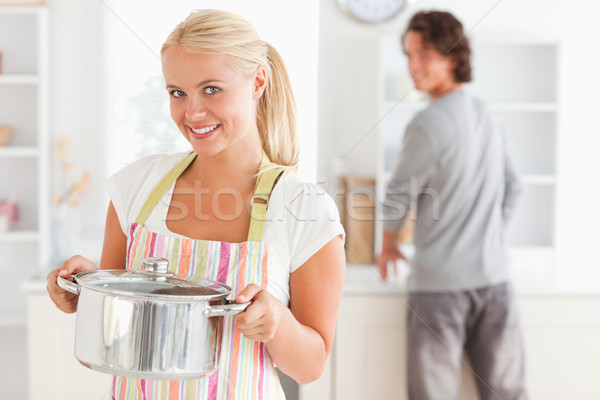 Portrait of a woman posing while a man is washing the dishes in their kitchen Stock photo © wavebreak_media