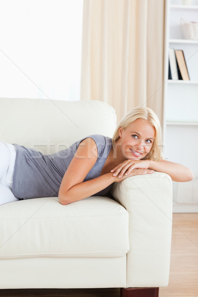 Portrait of a beautiful woman lying on a sofa while looking away from the camera Stock photo © wavebreak_media