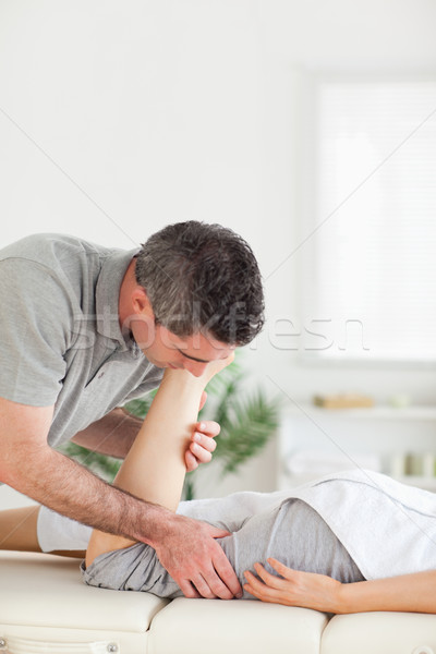 A customer's leg is stretched by a chiropractor Stock photo © wavebreak_media