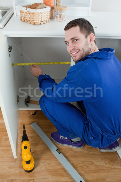 Portrait of a smiling repair man measuring something in a kitchen Stock photo © wavebreak_media