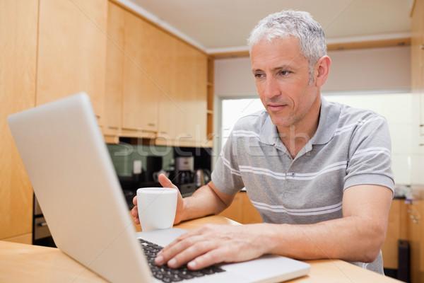 Adam dizüstü bilgisayar kullanıyorsanız içme kahve mutfak Internet Stok fotoğraf © wavebreak_media