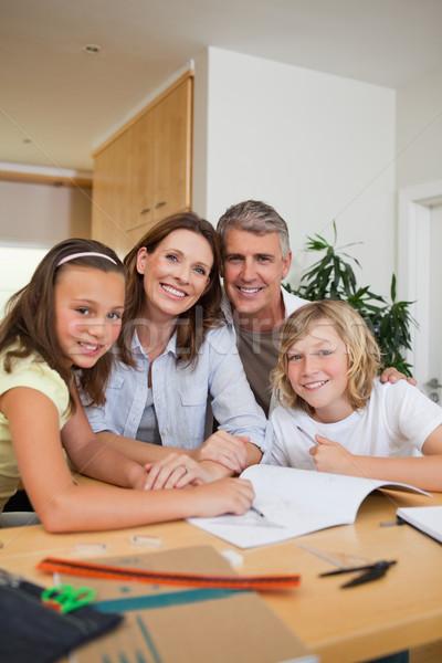 Sonriendo familia deberes junto libro nino Foto stock © wavebreak_media