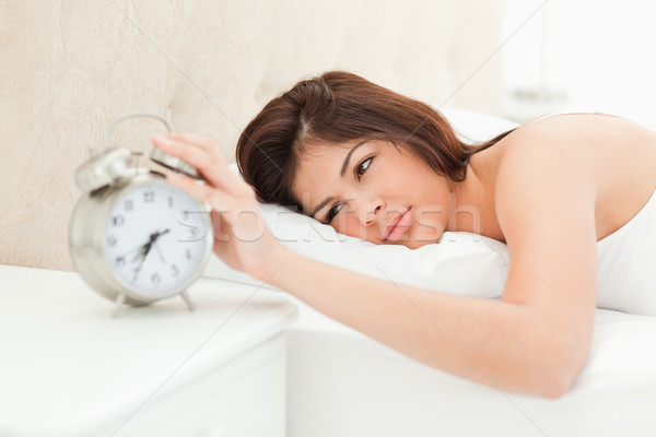 A woman lying on a bed with her hand on the bell of the nearby alarm clock to cease its ringing. Stock photo © wavebreak_media