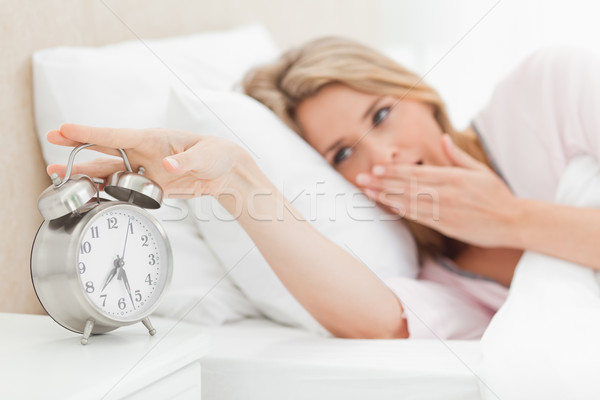 A woman in bed yawning and reaching over to silence the ringing alarm clock beside her bed. Stock photo © wavebreak_media