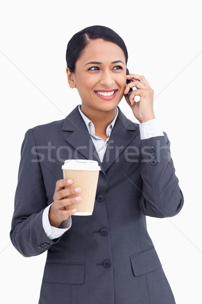 Close up of saleswoman with paper cup on her cellphone against a white background Stock photo © wavebreak_media