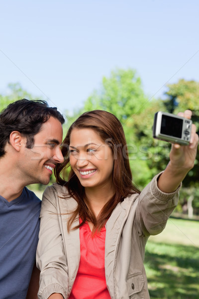 Stock photo: Young woman and her friend look at each other while she takes a photo of them together using her cam