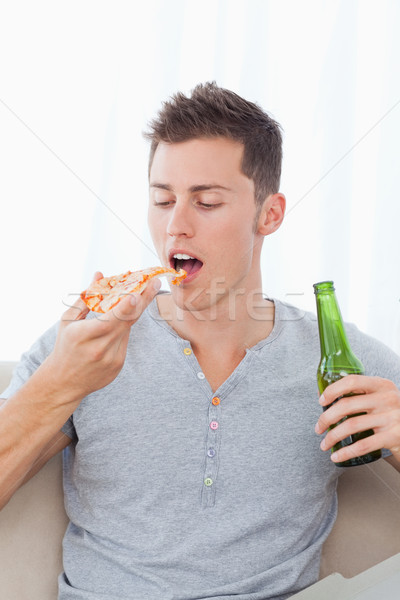 A man holding some beer in his hand as he is about to eat some pizza Stock photo © wavebreak_media