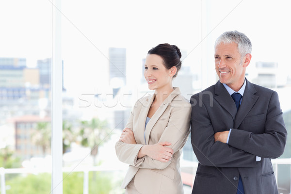 Stock photo: Business people crossing their arms while looking towards the side and smiling