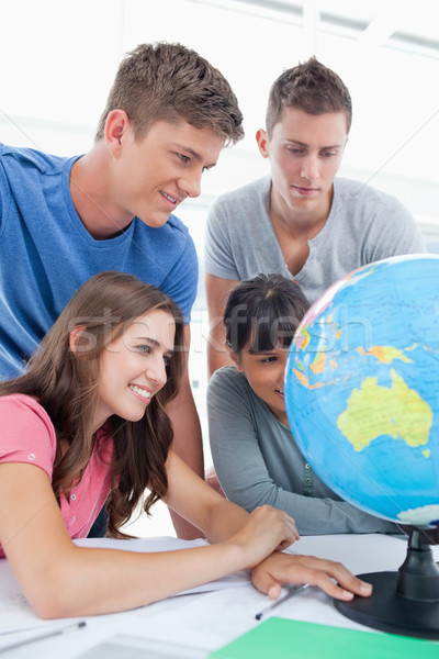 A close up shot of people looking at the globe in front of them Stock photo © wavebreak_media