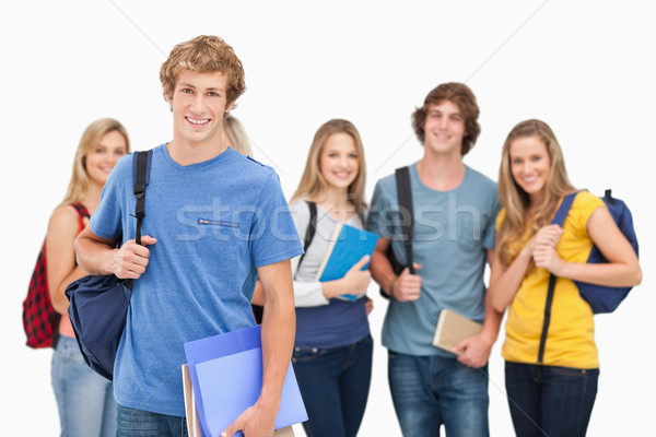 A smiling group of students all looking at the camera while one man stands in front of the rest of t Stock photo © wavebreak_media