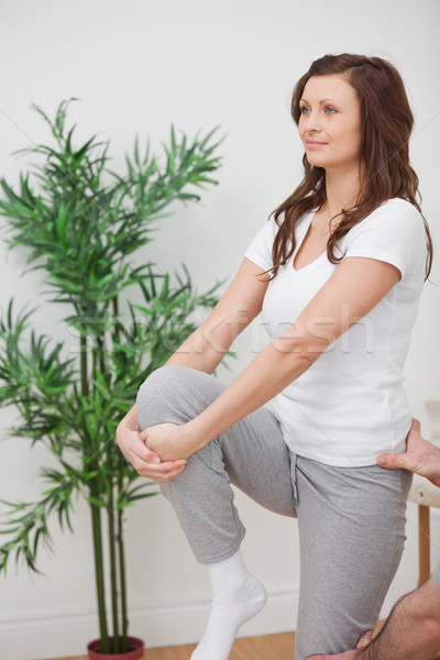Woman standing while stretching her leg in a room Stock photo © wavebreak_media