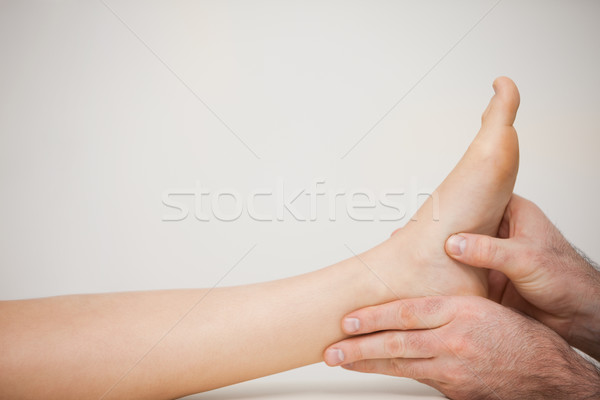 Chiropodist examining the foot of a patient in a medical room Stock photo © wavebreak_media