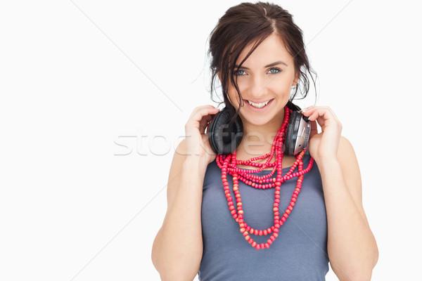 Blue eyed student holding her headphones against white background Stock photo © wavebreak_media