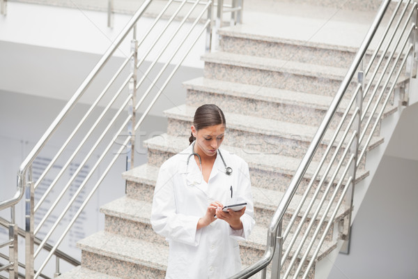 Doctor using a tablet computer on stairs in hospital  Stock photo © wavebreak_media