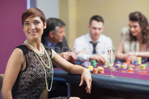 Smiling woman taking break from roulette with champagne in casino Stock photo © wavebreak_media