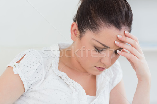 Exhausted woman sitting in a house and holding her hand against her head Stock photo © wavebreak_media