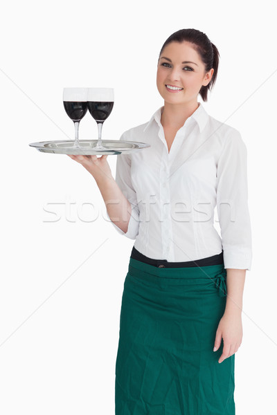 Smiling woman holding silver tray with glasses of red wine while directly looking into the camera Stock photo © wavebreak_media