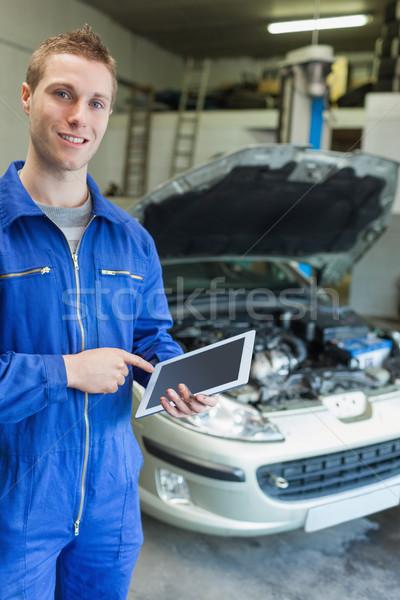 Happy mechanic using tablet computer Stock photo © wavebreak_media