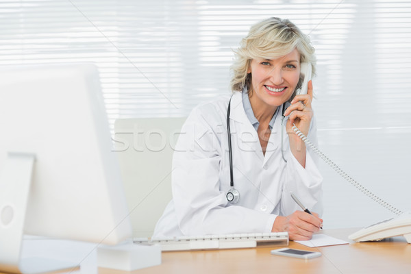 Stock photo: Smiling doctor with computer using phone at medical office