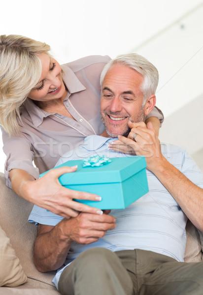 Gülümseyen kadın şaşırtıcı olgun adam hediye kanepe portre Stok fotoğraf © wavebreak_media