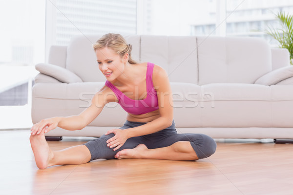 Fit blonde sitting on floor stretching her leg Stock photo © wavebreak_media