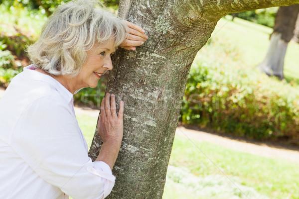 Thoughtful senior woman leaning to tree at park Stock photo © wavebreak_media