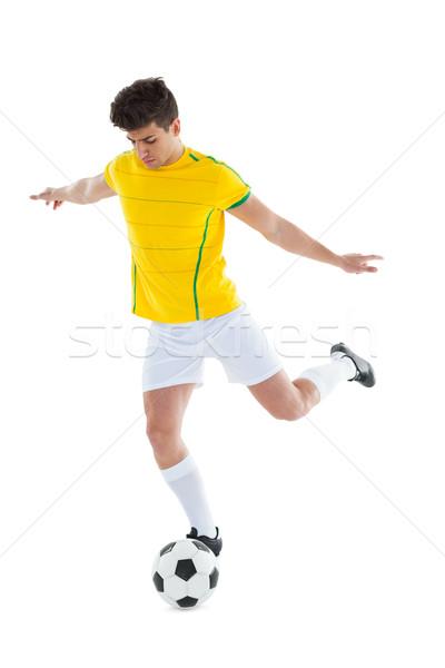 Football player in yellow jersey kicking ball Stock photo © wavebreak_media