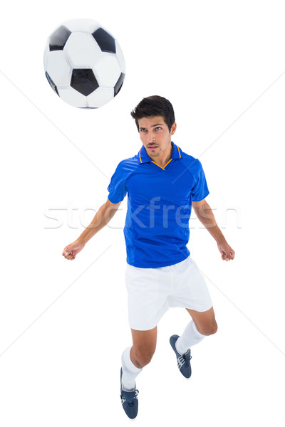 Football player in blue heading ball Stock photo © wavebreak_media