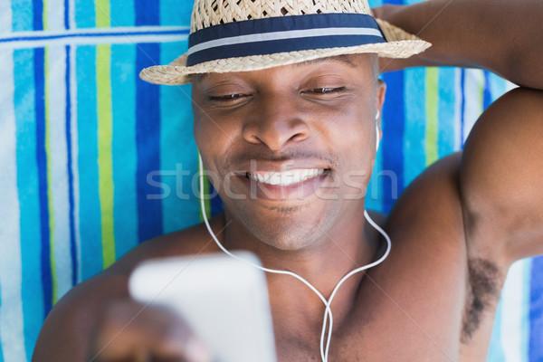 Handsome shirtless man listening to music poolside Stock photo © wavebreak_media