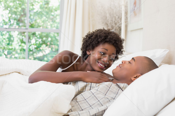 Happy couple lying in bed cuddling Stock photo © wavebreak_media