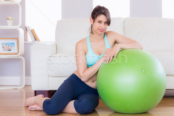 Fit brunette leaning on exercise ball smiling at camera Stock photo © wavebreak_media