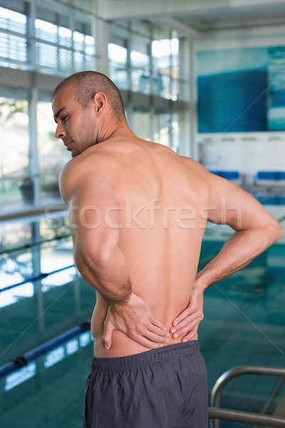 Rear view of shirtless swimmer with back ache by pool Stock photo © wavebreak_media