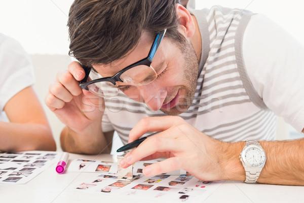 Photo editor using a magnifying loupe Stock photo © wavebreak_media