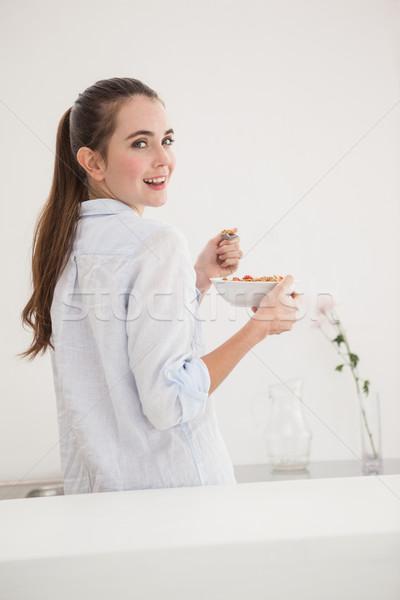 Mooie brunette eten kom granen home Stockfoto © wavebreak_media