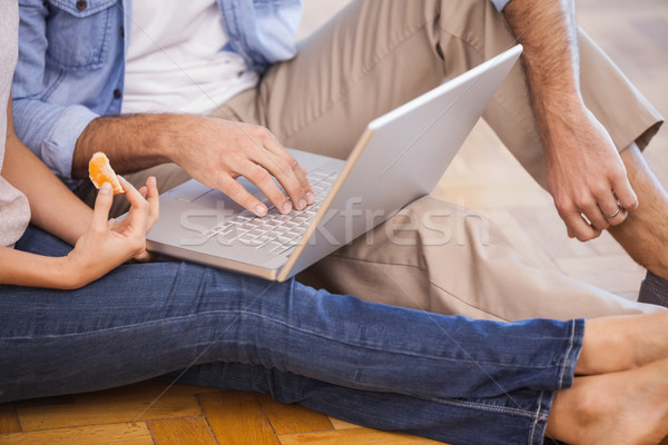 Mid section of couple sitting on floor using laptop Stock photo © wavebreak_media