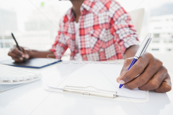 Designer taking notes and using digitizer Stock photo © wavebreak_media