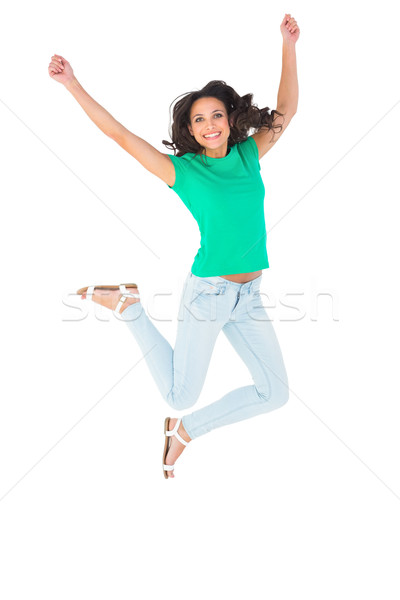 Pretty brunette jumping and smiling Stock photo © wavebreak_media