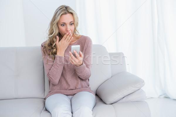 驚いた ブロンド 座って ソファ 読む メッセージ ストックフォト © wavebreak_media