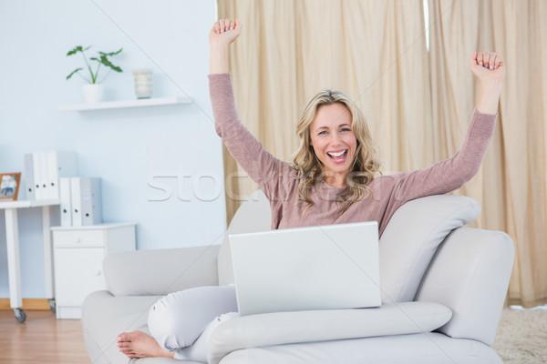 Smiling blonde cheering and using laptop Stock photo © wavebreak_media
