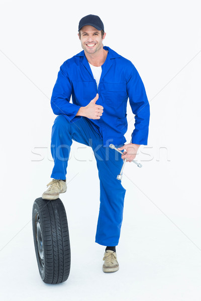 Mechanic with tire and wheel wrenches gesturing thumbs up Stock photo © wavebreak_media